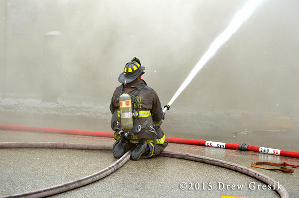 fireman with hose in smoke