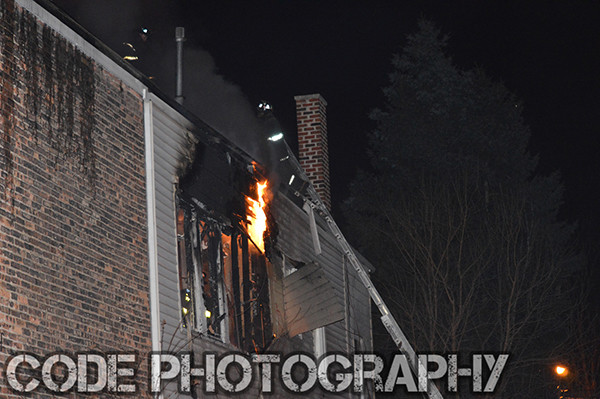 fireman on ladder at night with flames