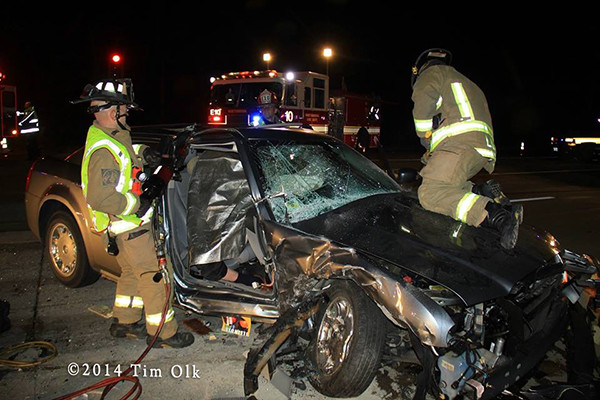 firemen cut crash victims from car at night