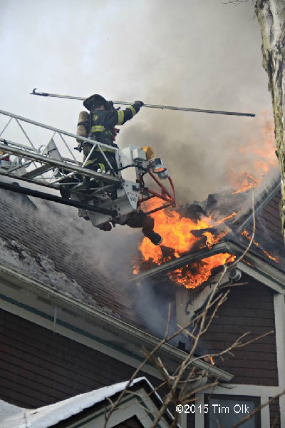 fireman on aerial ladder with heavy smoke and fire