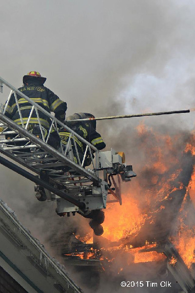 firemen on aerial ladder with heavy smoke and fire