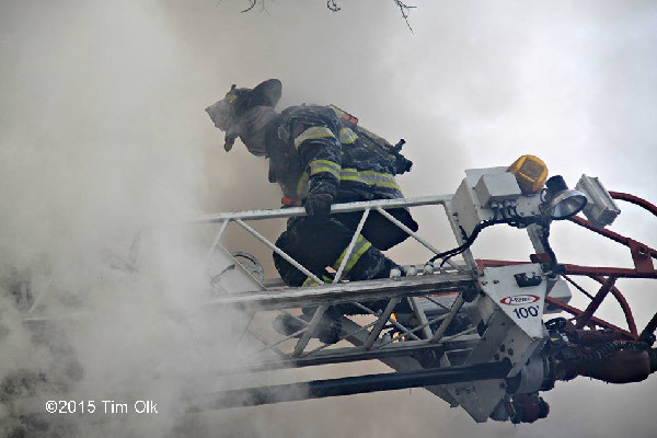fireman on aerial ladder with heavy smoke