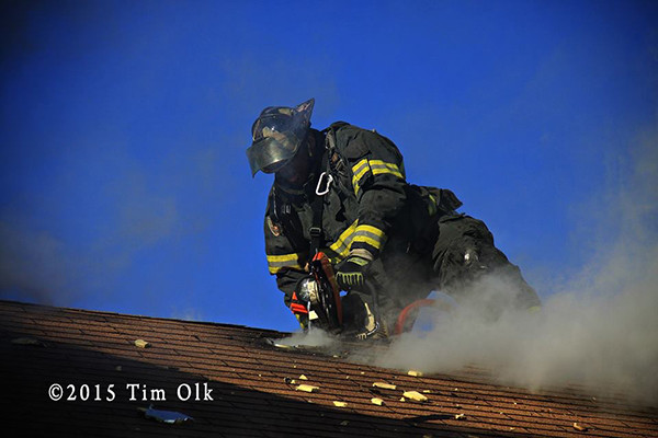 fireman vents roof with saw at house fire
