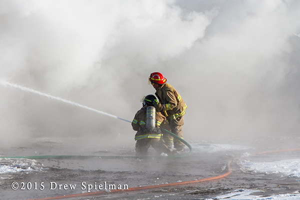 firemen with hose in smoke at fire scene