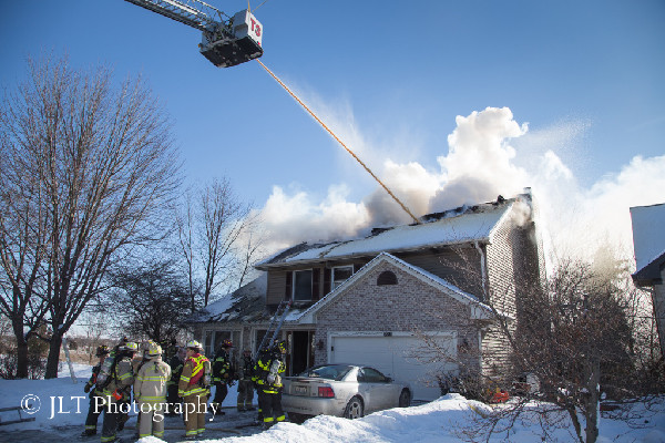 firemen pour water on house fire