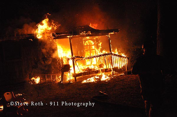 house fully-engulfed in flames at night