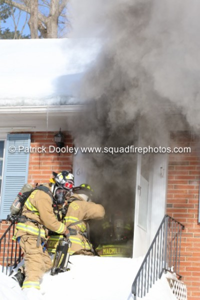 firemen take a line into a house with heavy smoke