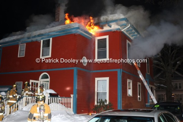flames throughout the roof of a house at night