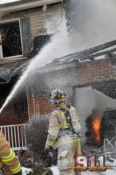 firemen use foam to fight a residential garage fire