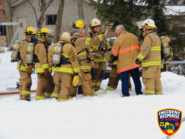 firemen in the snow at a house fire