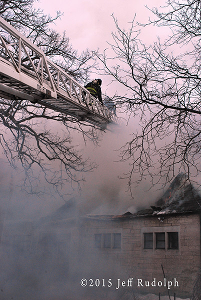 aerial fire ladder with firemen in smoke