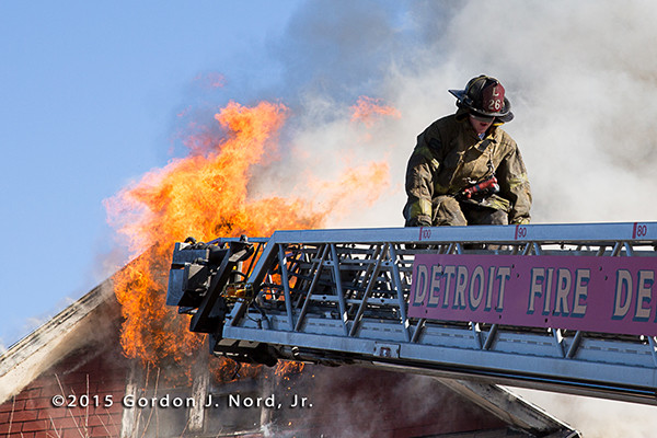 Detroit fireman on a ladder with heavy fire