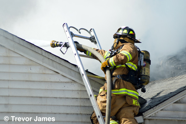 fireman at house fire on ladder with hose