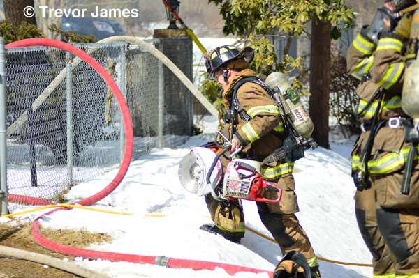 fireman carries saw through snow at house fire