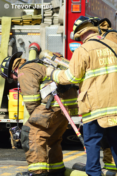 firemen change out air bottle at fire scene