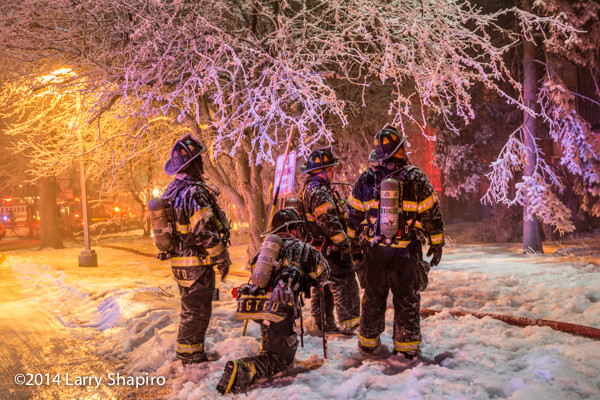 firemen and trees covered with ice at winter fire scene