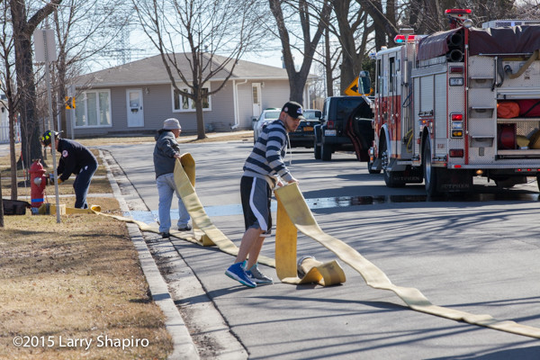 civilians help pull fire hose
