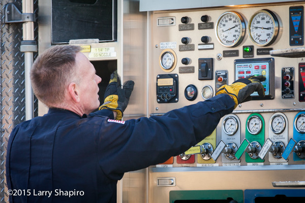 fireman at pump panel of fire engine