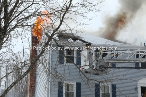 flames through the roof of a two-story house