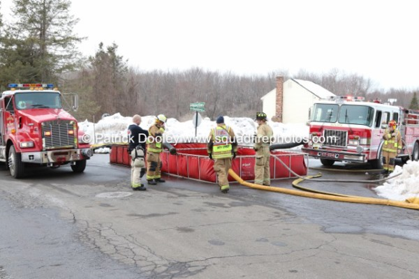 firemen setup portable tank at fire scene for drafting water from tankers