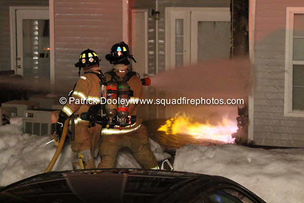 firemen fight flames at a house at night