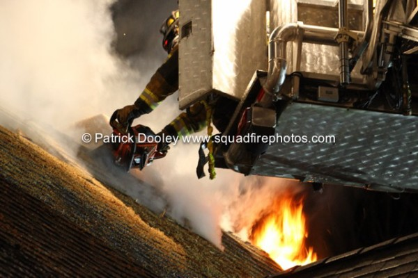fireman vents roof at night with flames