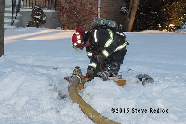 fireman connects hose to hydrant buried by snow