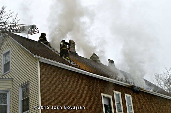 firemen on roof vent house with smoke
