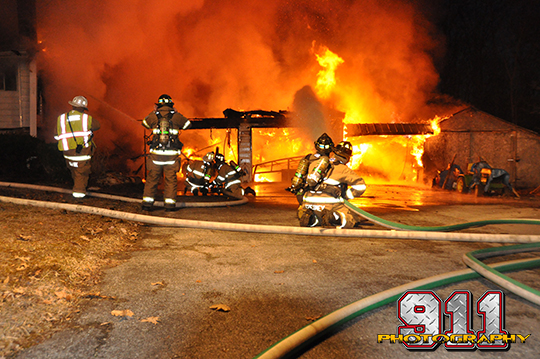 firemen battle a house fyllu engulfed in flames at night