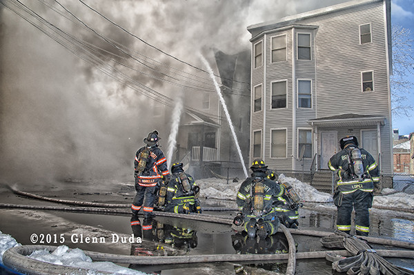 firemen working at a fire scene with heavy smoke
