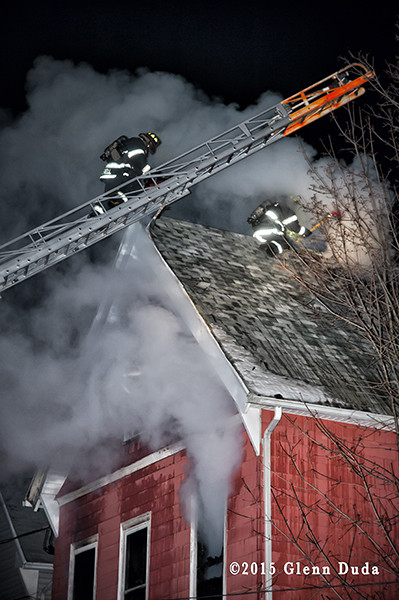 fireman climbs Seagrave aerial ladder at night fire scene