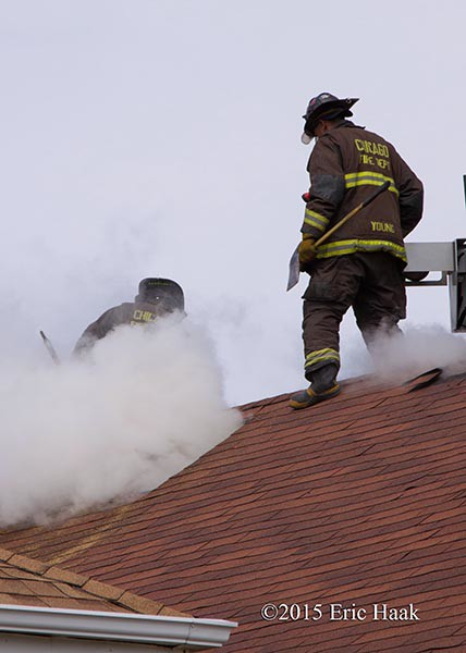 firemen venting roof with smoke