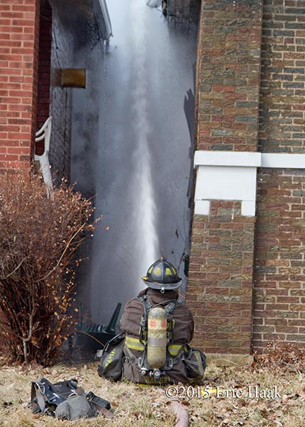 fireman using hose line at fire scene