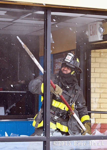 fireman breaks windows at commercial fire scene