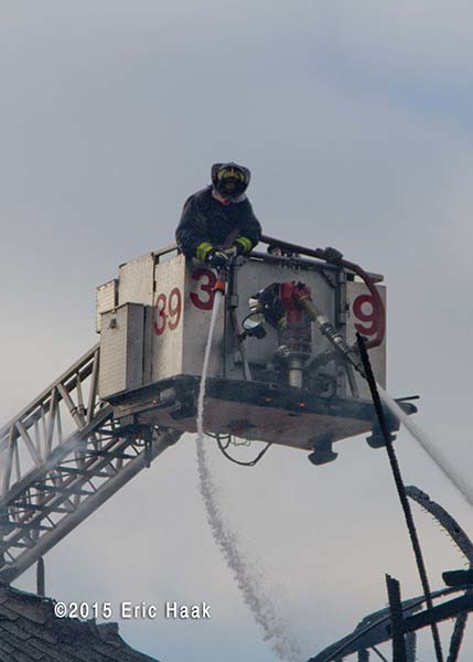 fireman using American LaFrance LTI tower ladder at fire scene