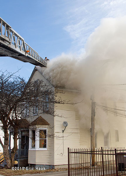aerial ladder to roof of smokey house fire