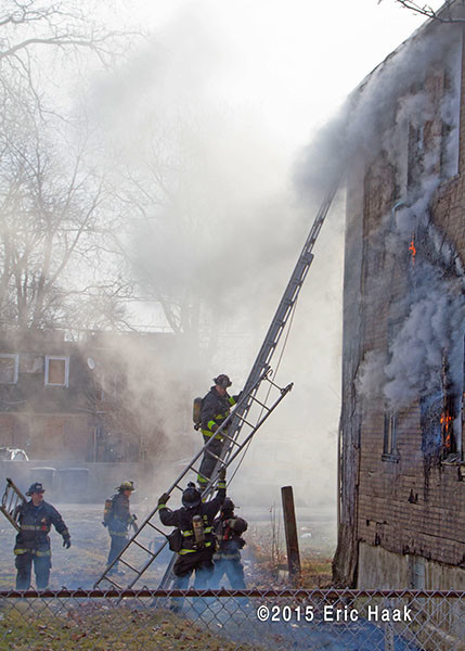 firemen climb ladder at smokey fire scene