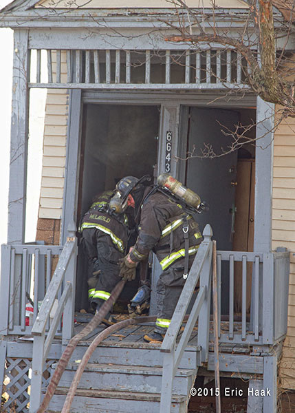 firemen take hose into burning house