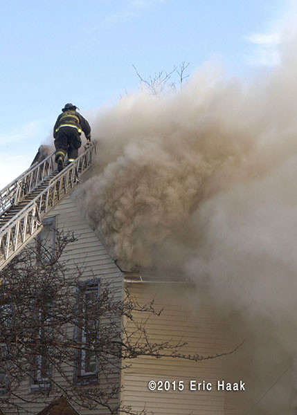 fireman climbing aerial ladder through heavy smoke