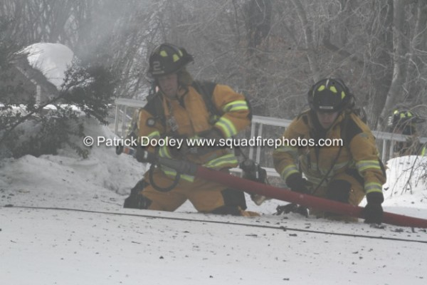 firemen with hose line in the winter