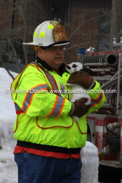 fire department chaplain carries family pet from house fire