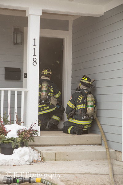 firemen make entry at house fire