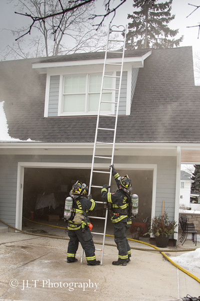 firemen raise a ground ladder at a house fire