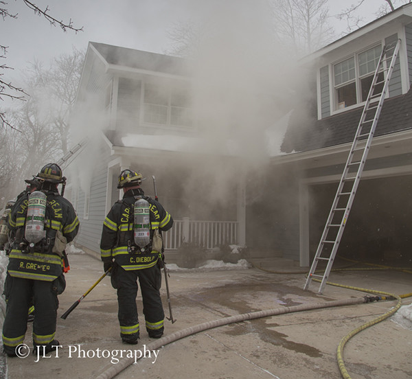 firemen at house fire with heavy smoke