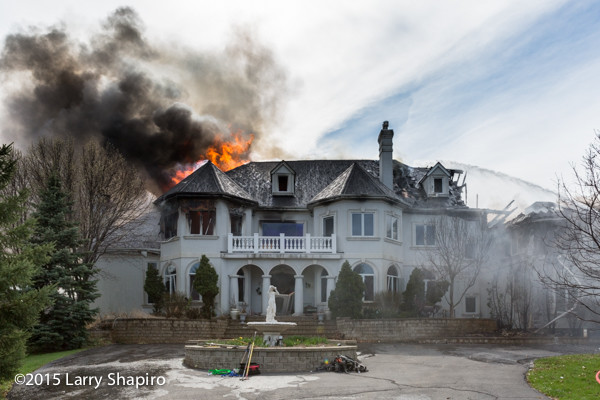 mansion on fire with heavy smoke and flames