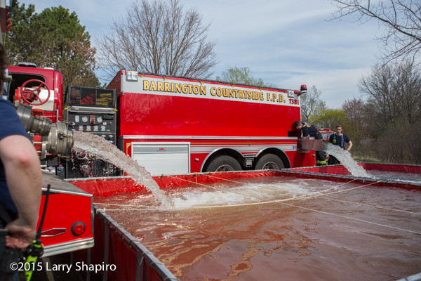 fire department water tenders dump into portable tanks