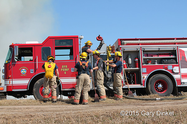 Canadian firemen work at grass fire