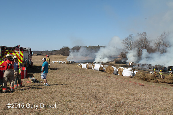 hundreds off rolled hay bales burn in a field
