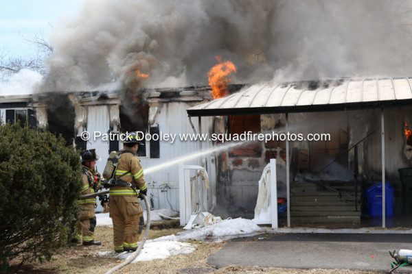 firemen battle a mobile home fire
