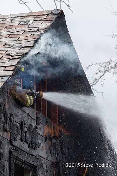fireman hitting hot spots after house fire